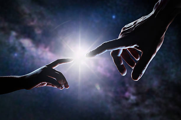 Hand Of God Close up of two hands, adult's and child's, reaching each other like Michelangelo's painting in front of stars and galaxy. Light is shining between father's and son's fingers. High contrast, lens flare. creation of the universe stock pictures, royalty-free photos & images