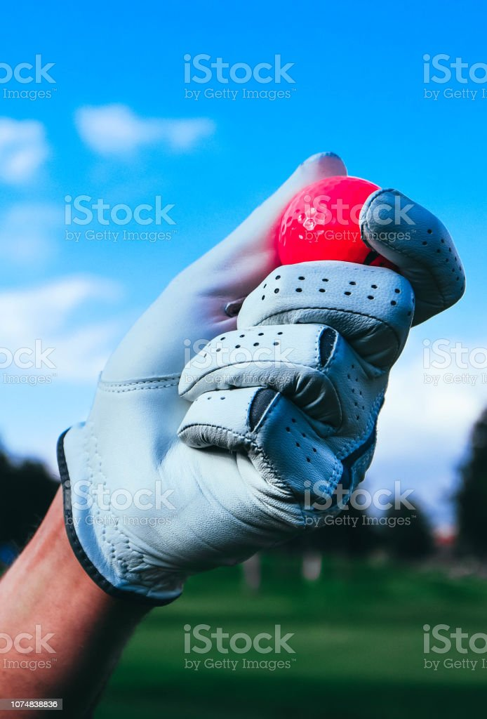 A hand of golfer in glove holding a red ball. Trees, mountain, golf...