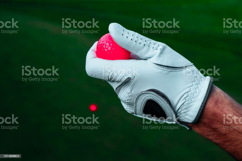 A hand of golfer with a glove and red ball, close up. Green golf...