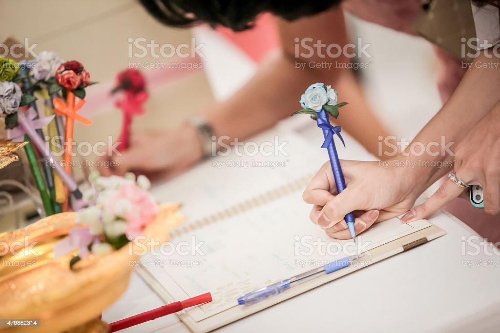 Hand of guests writing on a Wedding Signing books stock photo