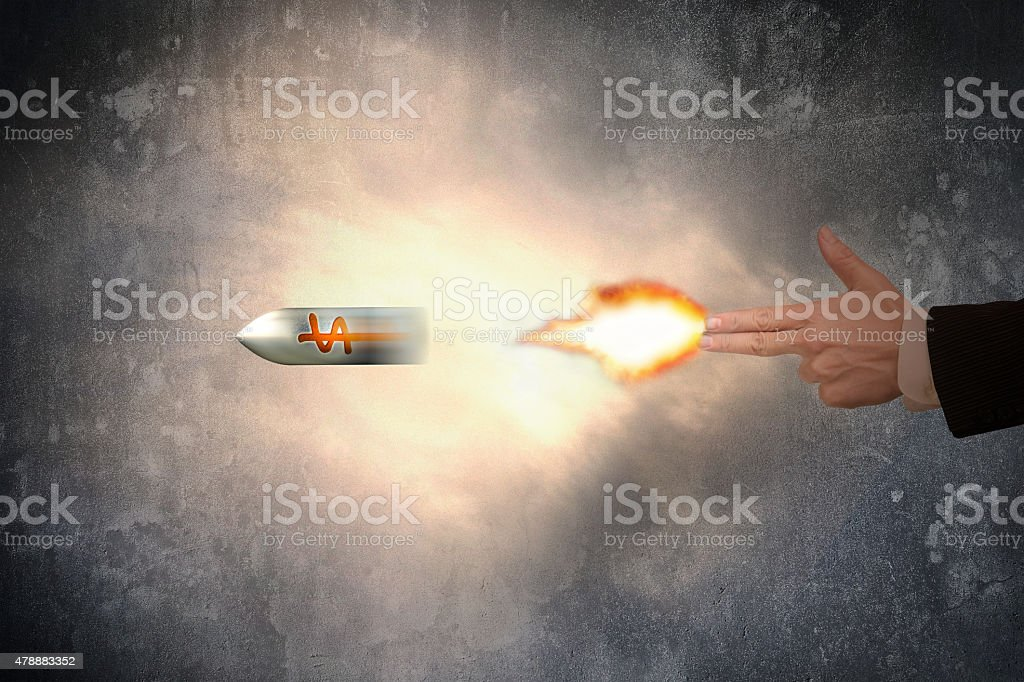 Hand of gun gesture with firelight shooting dollar sign bullet stock photo