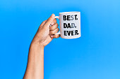 istock Hand of hispanic man holding best dad ever coffee cup over isolated blue background. 1281100613