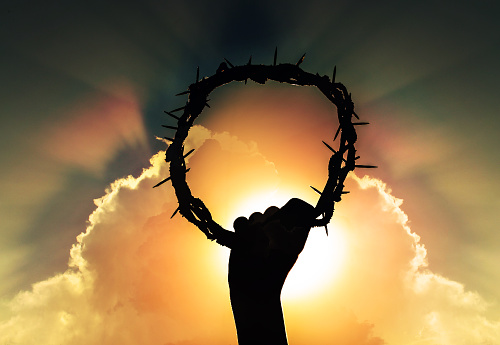 hand of Jesus christ with sky and rising sun, holding crown of thorns, critsão symbol of rebirth, faith and easter