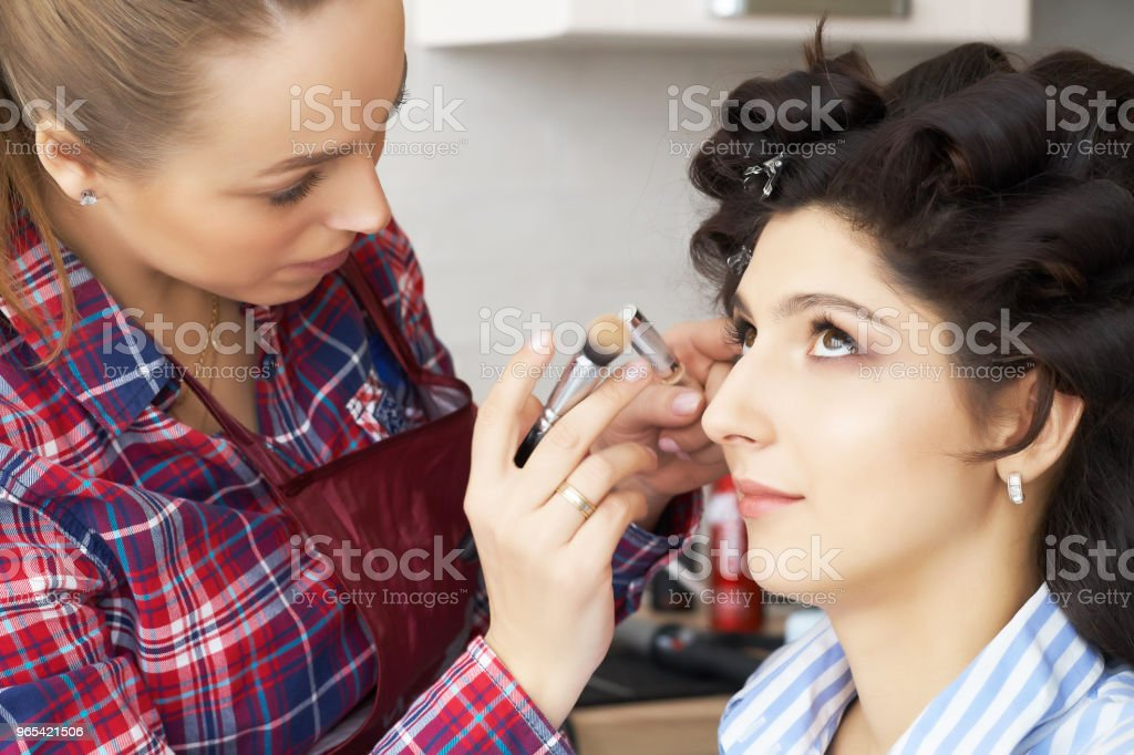 Main de maître de maquillage peinture, maquillage en cours. Artiste maquilleur vaut mascara pour les cils de la jeune fille modèle. Visage de belle femme - Photo de Adulte libre de droits