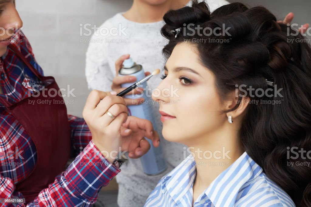 Hand of make-up master painting, make up in progress. Makeup artist applies mascara to the eyelashes of the model girl . Beautiful woman face royalty-free stock photo