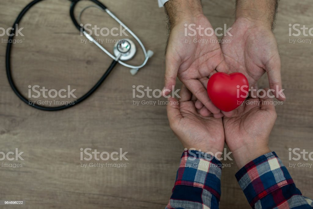 Hand of male doctor and patient holding heart with stethoscope on the desk, closeup royalty-free stock photo