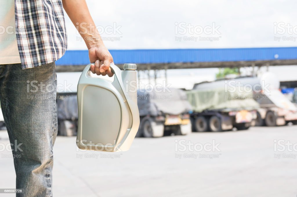 Hand of male holing gray plastic canister of motor oil on gas station background stock photo