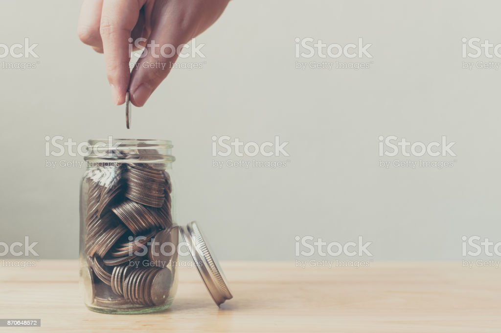 Hand of male or female putting coin in jar for saving money, Concept finance business investment stock photo