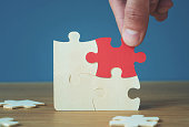 istock Hand of male or female putting jigsaw puzzle connecting on woodden desk, Strategic management and business solutions for success 1158066798