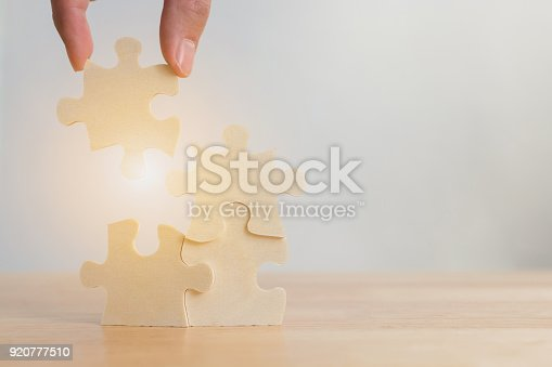 istock Hand of male or female putting jigsaw puzzle connecting on woodden desk, Strategic management and business solutions for success 920777510