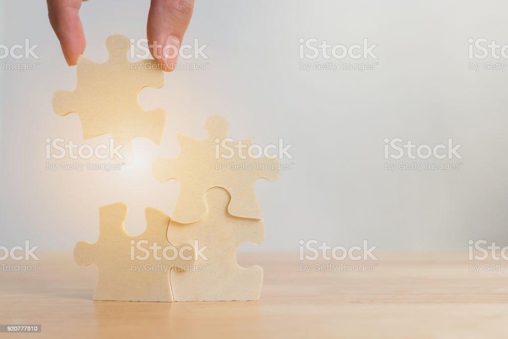 Hand des männlichen oder weiblichen setzen Jigsaw Puzzle auf woodden Schreibtisch, strategisches Management und Business-Lösungen für den Erfolg – Foto
