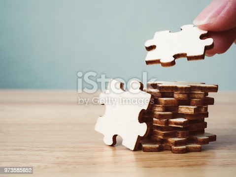 istock Hand of male or female putting jigsaw puzzle connecting on wooden desk and wall background, Strategic management and business solutions for success 973585652