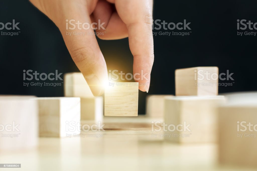Hand of male pick up on one wooden block from many, Business ideas for choosing something that looks distinctive concept stock photo