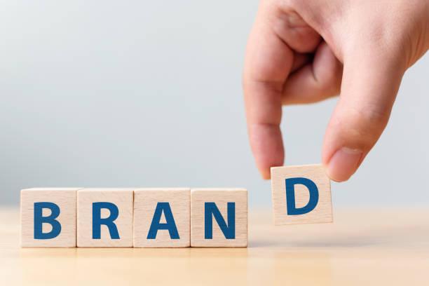 """木製のテーブルの上に単語 """"ブランド"""" と木製の立方体のブロックを置く男性の手。成功コンセプトのブランド構築 - 広告 ストックフォトと画像"""