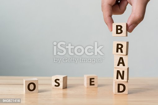 "istock Hand of male putting wood cube block with word ""BRAND"" on wooden table. Brand building for success concept 940821416"