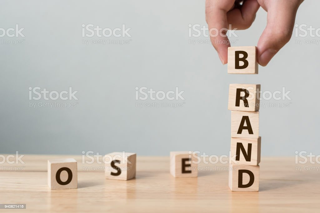 """Hand of male putting wood cube block with word """"BRAND"""" on wooden table. Brand building for success concept stock photo"""