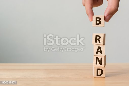 "istock Hand of male putting wood cube block with word ""BRAND"" on wooden table. Brand building for success concept 950216174"