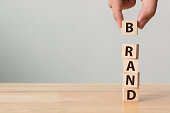 "Hand of male putting wood cube block with word ""BRAND"" on wooden table. Brand building for success concept"