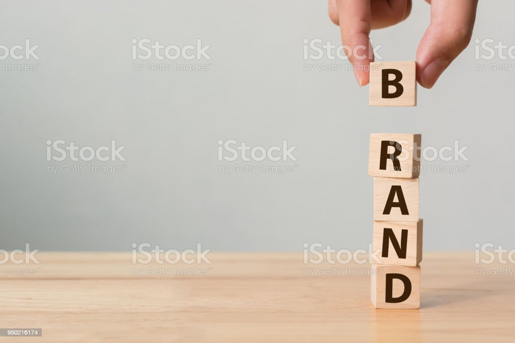 "Hand of male putting wood cube block with word ""BRAND"" on wooden table. Brand building for success concept stock photo"