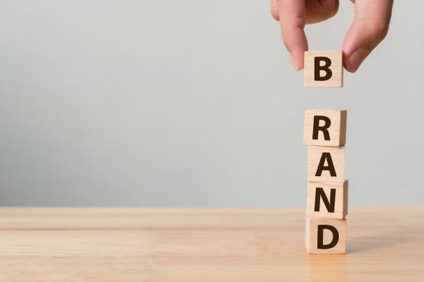"hand of male putting wood cube block with word ""brand"" on wooden table. brand building for success concept - advertisement stock photos and pictures"