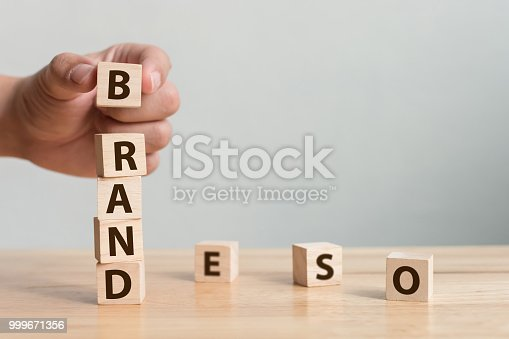 "istock Hand of male putting wood cube block with word ""BRAND"" on wooden table. Brand building for success concept 999671356"