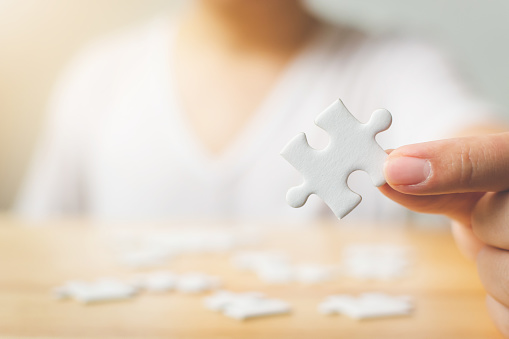 istock Hand of male trying to connect pieces of white jigsaw puzzle on wooden table. Healthcare for alzheimer disease, dementia, memory loss, autism awareness and mental health concept 1056791052