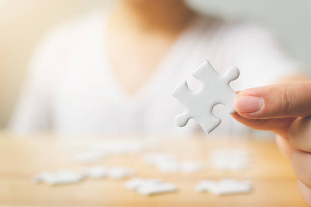 Hand of male trying to connect pieces of white jigsaw puzzle on wooden table. Healthcare for alzheimer disease, dementia, memory loss, autism awareness and mental health concept stock photo