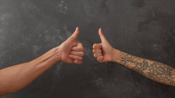 hand of man and female hand with tattoo - tattoo removal stock pictures, royalty-free photos & images