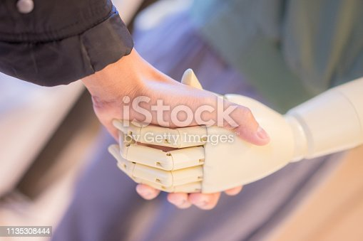 istock hand of man and the robot that is held together is the promise of life's agreement. 1135308444