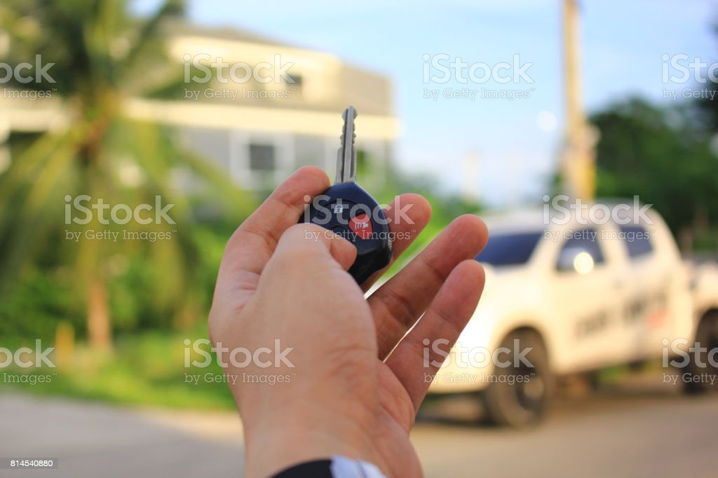 Hand of man holding car remote control pointing to car door open, Car...