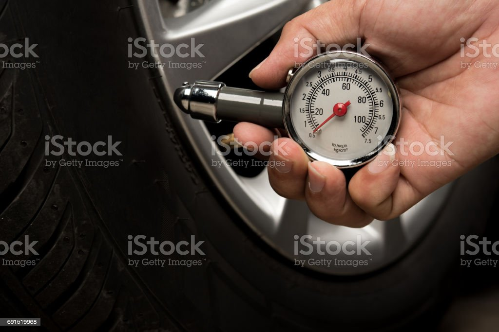 Hand of man holding gauge measurement pressure checking tire of car transportation knowledge stock photo