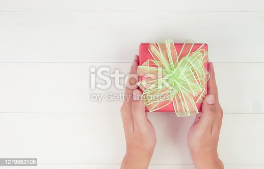 Hand of man holding gift giving on wooden table in Christmas day or holiday, present box for anniversary or birthday or celebration with copy space, celebrate and festive, top view, flat lay.