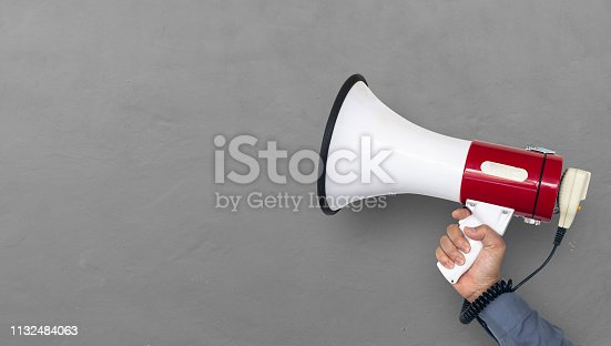istock hand of man holding megaphone on brick wall background 1132484063
