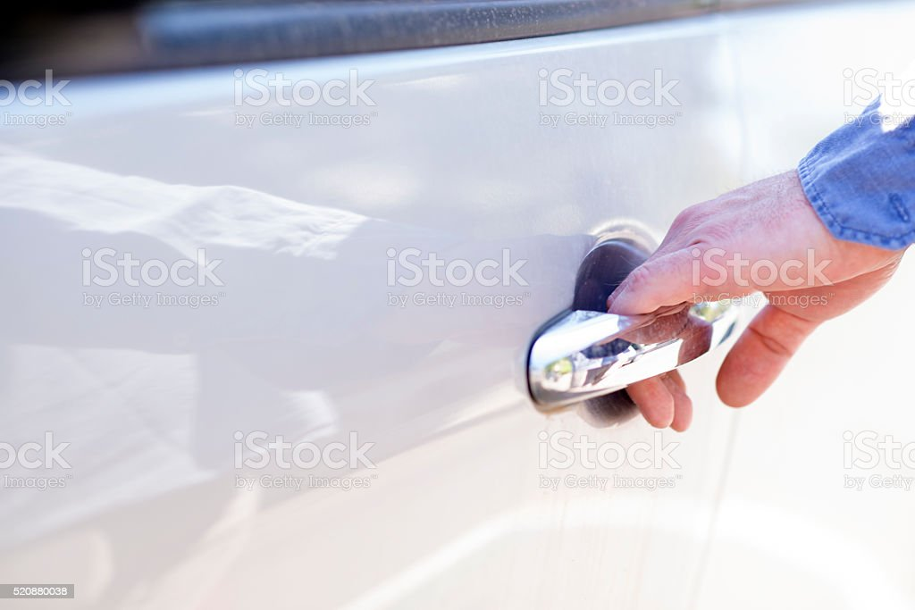 Hand of man opening a car door stock photo