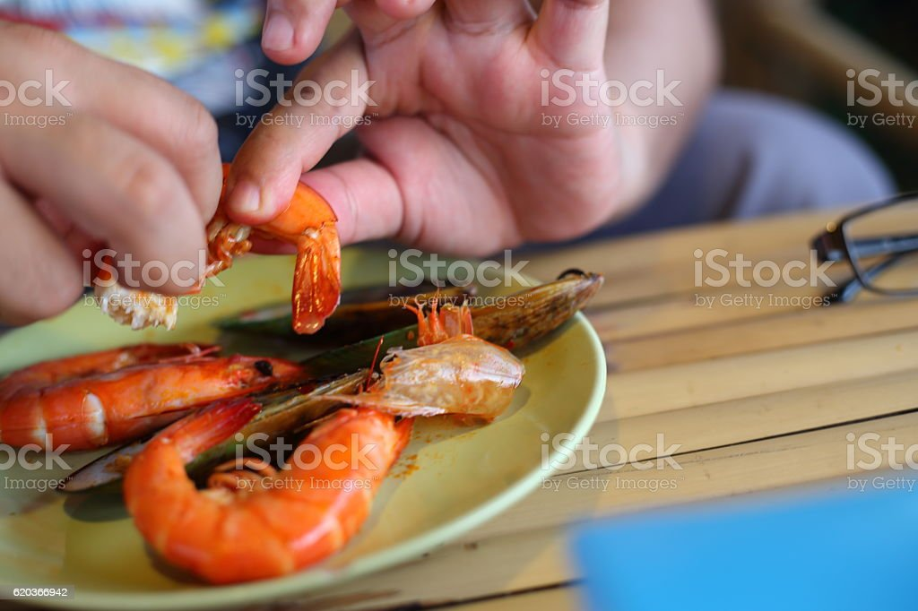Hand of man peeled shrimps on the plate zbiór zdjęć royalty-free