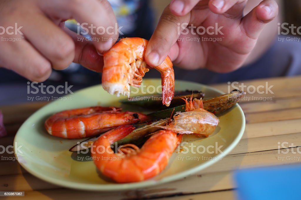 Hand of man peeled shrimps on the plate foto de stock royalty-free