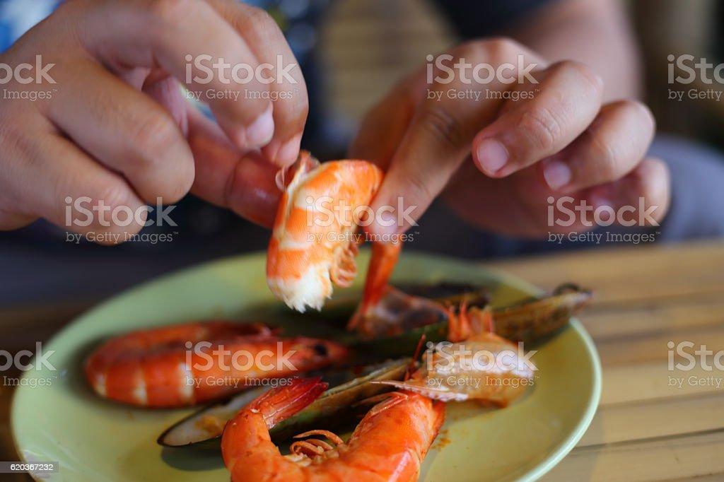 Hand of man peeled shrimps on the plate zbiór zdjęć royalty-free
