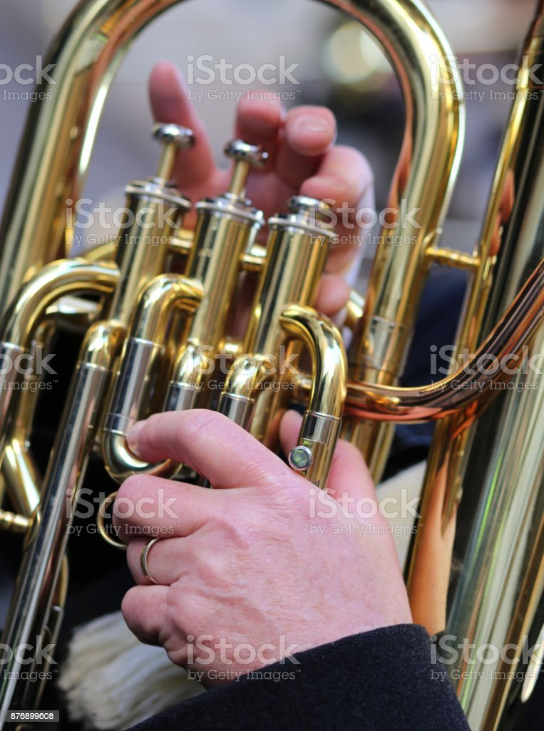 hand of man plays the trombone in the brass band stock photo