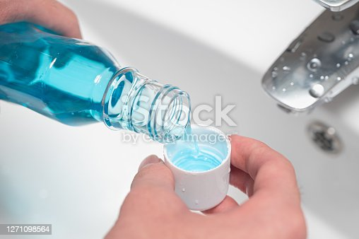 Hand of man Pouring Bottle Of Mouthwash Into Cap.