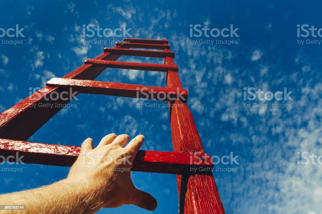 Hand Of Man Reaching For Red Ladder Leading To A Blue Sky. Development motivation Career Growth Concept - Royalty-free Achievement Stock Photo