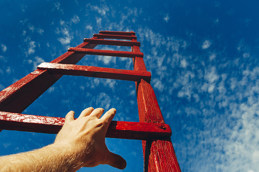 Hand Of Man Reaching For Red Ladder Leading To A Blue Sky Development Motivation Career Growth Concept Stock Photo - Download Image Now