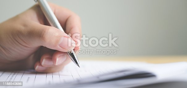istock Hand of man signing signature filling in application form document business contract agreement 1188540686