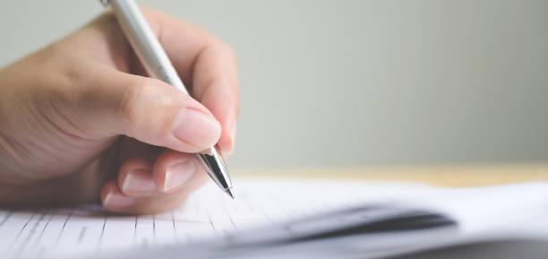 Mano del hombre firmando la firma rellenando el formulario de solicitud contrato de contrato comercial - foto de stock