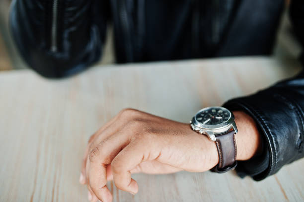Hand of man wear leather jacket looking at watches. stock photo