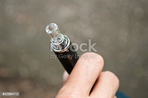 830035654istockphoto hand of man with e-cigarette 842394112