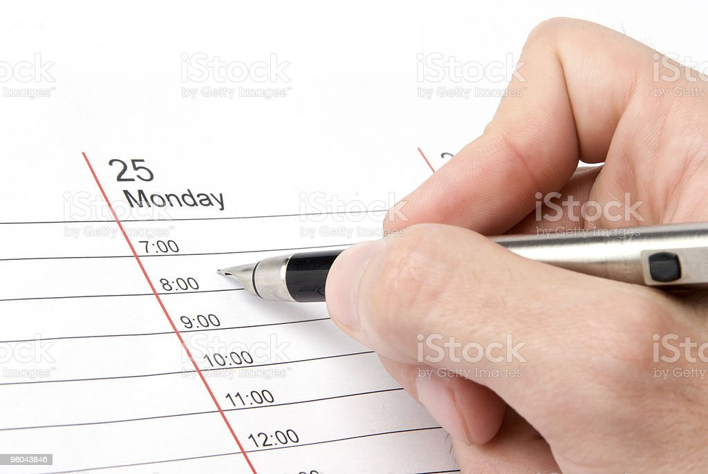 Hand of man writing in day planner royalty-free stock photo