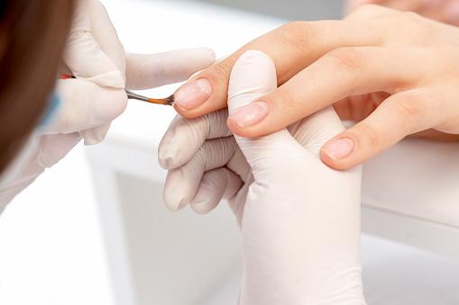 istock Hand of manicurist applying clear nail polish 1250022663