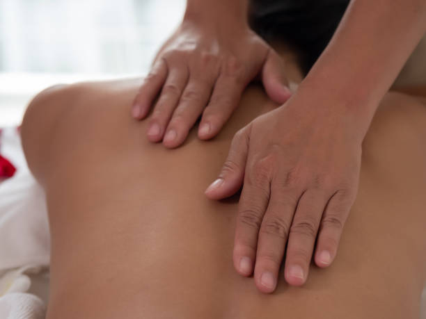 Hand of masseuse's on the backs of Asian woman are a relaxing on bed. Massage and body care. Spa in salon stock photo