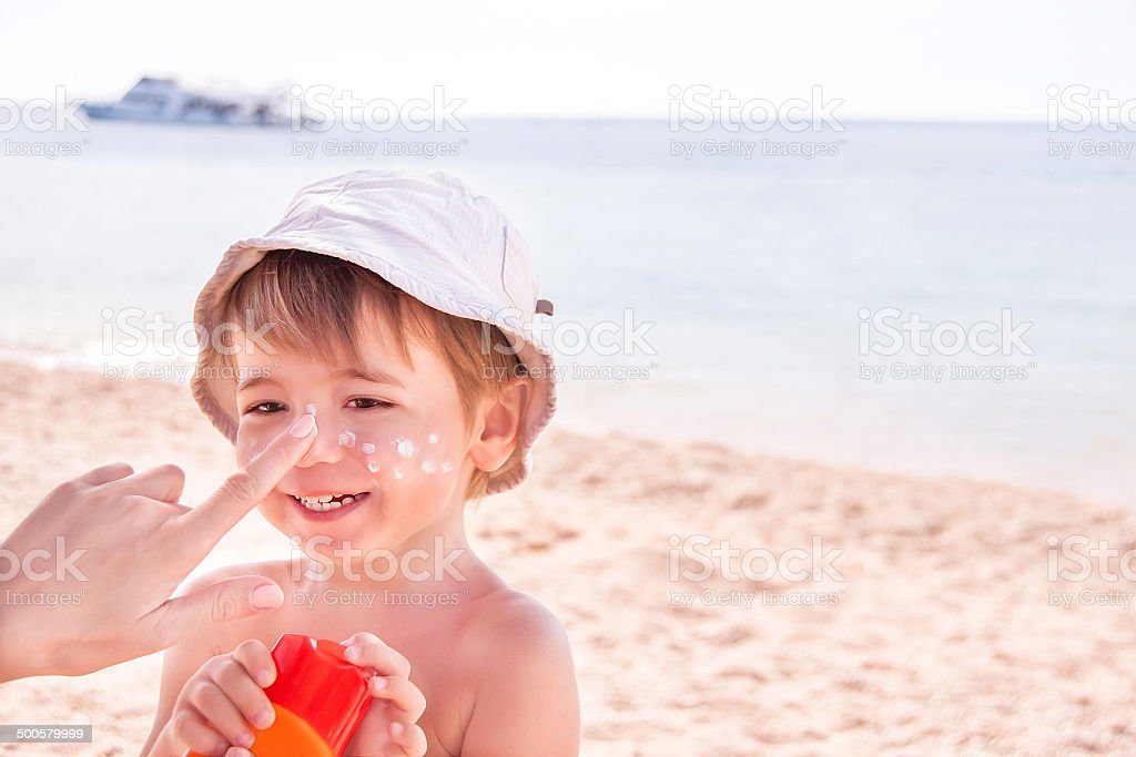 Hand of mother applying suncream to her son on beach. stock photo