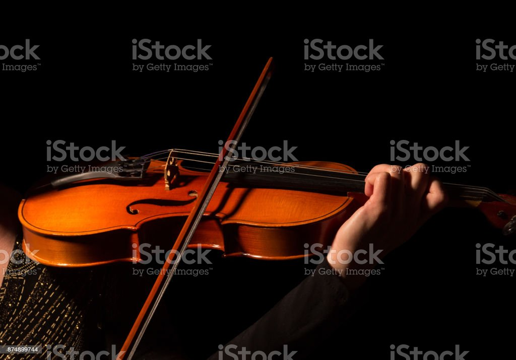 Hand of musician playing the violin isolated on black stock photo